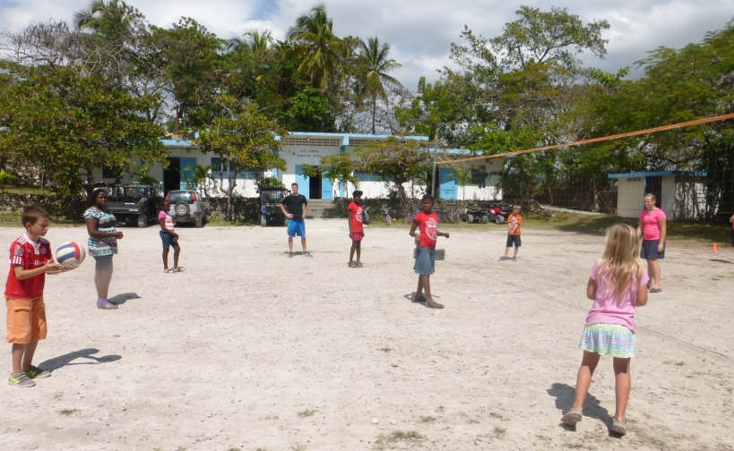 """Mr. Grant"" teaching volleyball in front of the Cite Lumiere Christian School!"