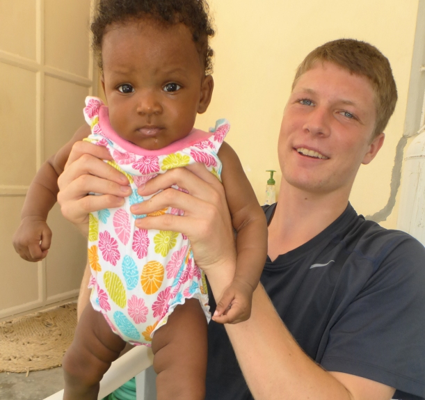 Grant, taking a break from school, to help babysit Bessakina, our cook's baby!