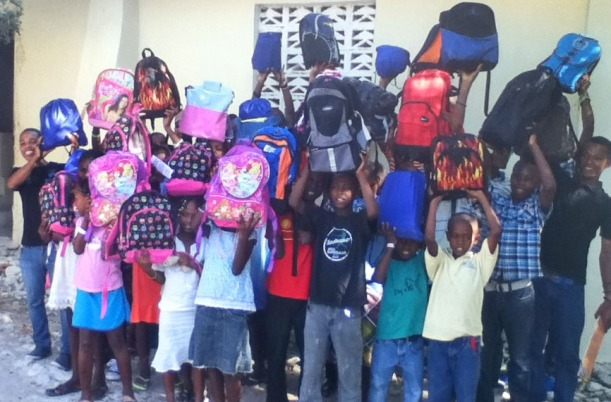 Before they left for home, the kids are showing off the book bags they won!