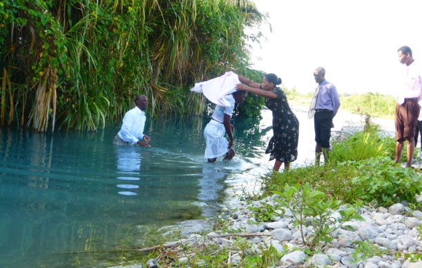 A typical baptism scene in Haiti. What is the first thing you notice that is similar to the baptisms you have seen? (Was it the towel?)